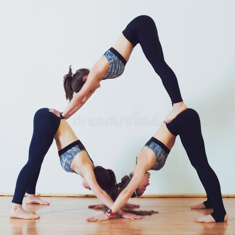 Acroyoga, yoga van de drie de sportieve meisjespraktijk in paar Partneryoga, vertrouwen, saldo en gezond levensstijlconcept Yogaf stock foto's