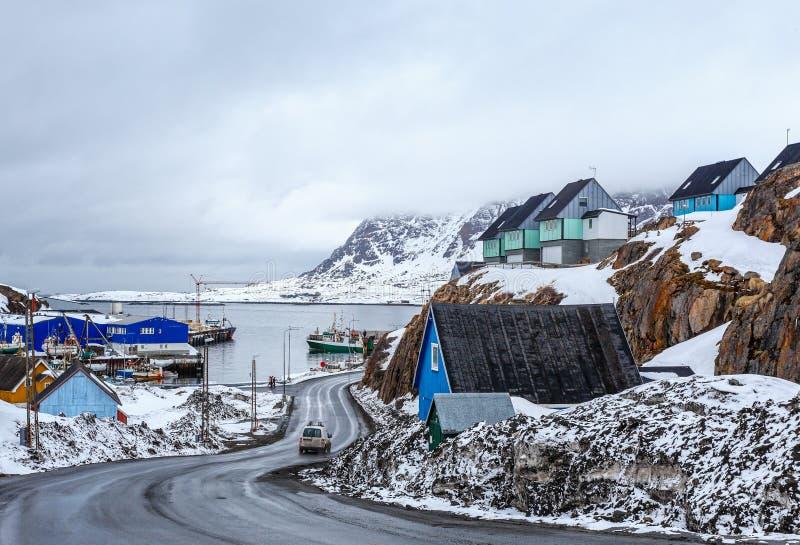 Acrticweg aan de dokken en de haven tussen de rotsen met Inuit-huizen, Sisimiut, Groenland stock fotografie