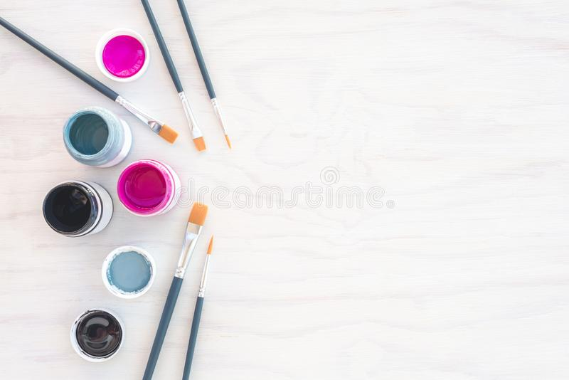 Acrylic paint and paintbrushes on white background royalty free stock image