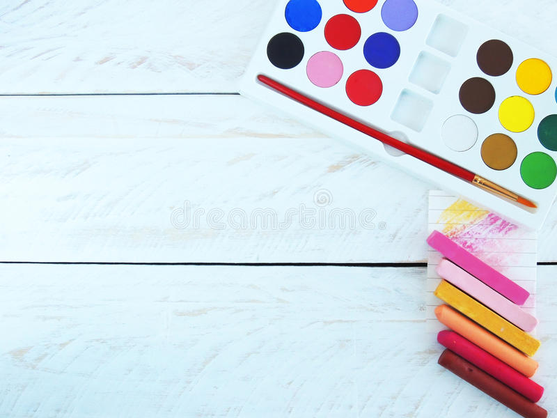 Acrylic paint set and soft and oil pastels. Styled stock photography with acrylic paint set, paintbrush, and soft and oil pastels, on a white wood background royalty free stock photography