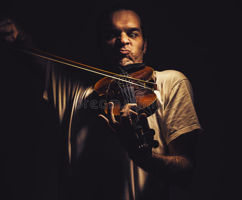 Act of a Violin Player. Adult man is playing a violin, in dark ambiance, showing emotions and expressions royalty free stock photos