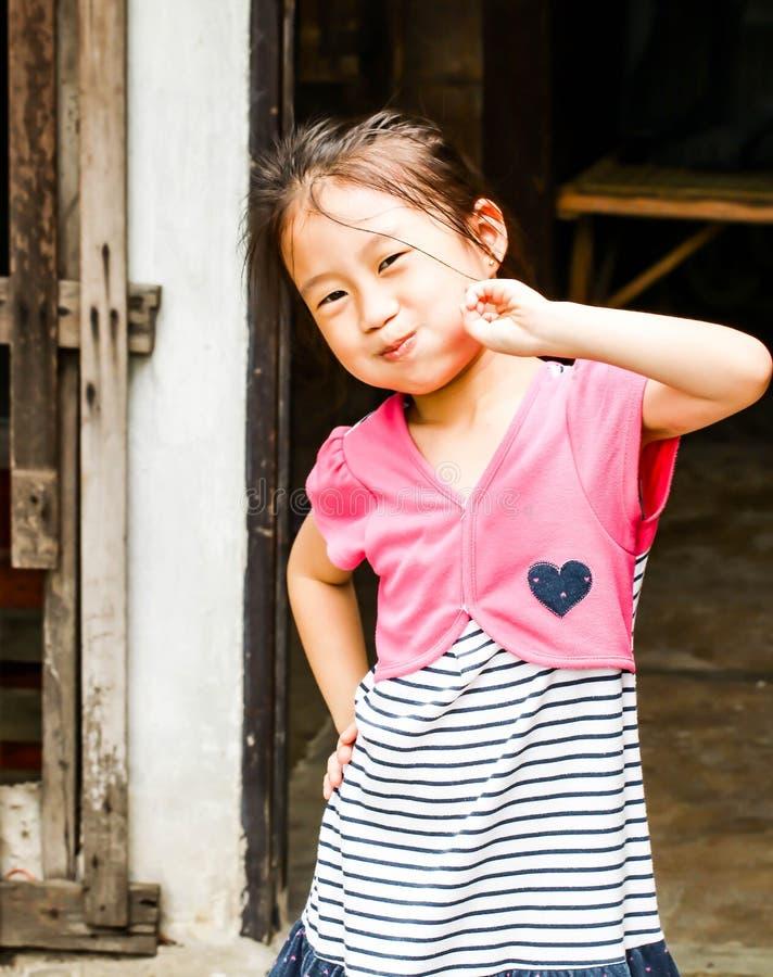 Acte mignon de fille de l'Asie à la robe rose de port innicent images libres de droits