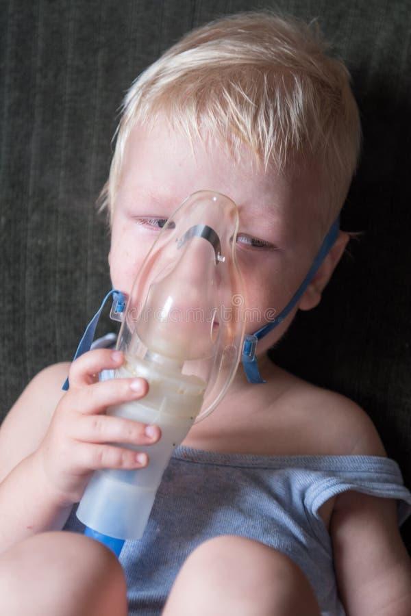 Actes médicaux inhalateur La blonde caucasienne inhale des couples contenant le médicament pour cesser la toux Le concept du trea photos libres de droits