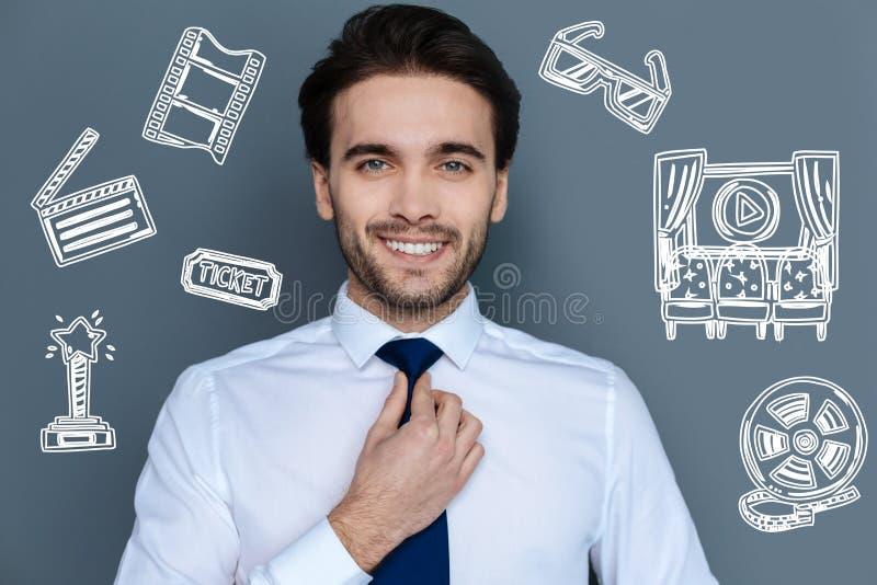 Acteur populaire touchant le sien lien tout en se préparant à un événement à la mode images stock