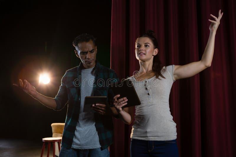 Acteurs préparant sur l'étape tout en à l'aide du comprimé numérique photographie stock