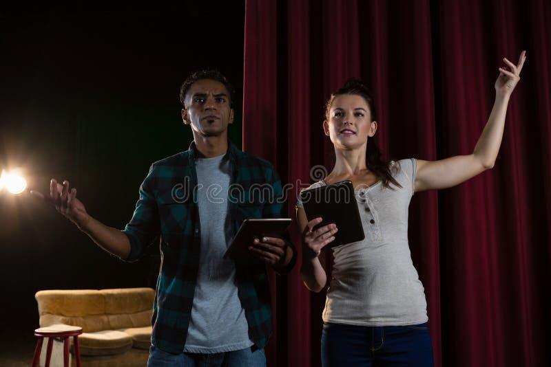 Acteurs préparant sur l'étape tout en à l'aide du comprimé numérique photographie stock libre de droits