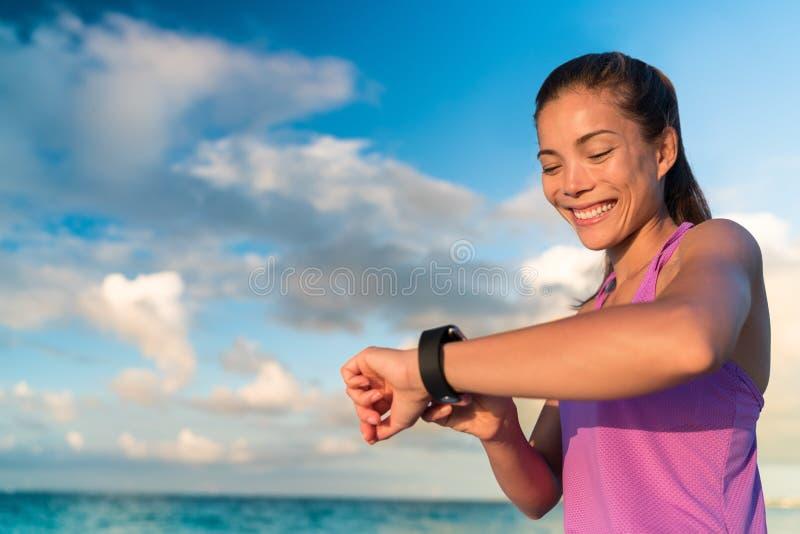 Actief Aziatisch meisje die het slimme horloge van de geschiktheidsdrijver met behulp van stock afbeelding