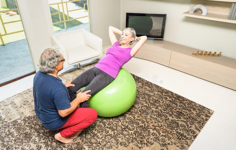 Actief bejaard paar bij geschiktheid opleiding met Zwitserse bal thuis stock afbeeldingen