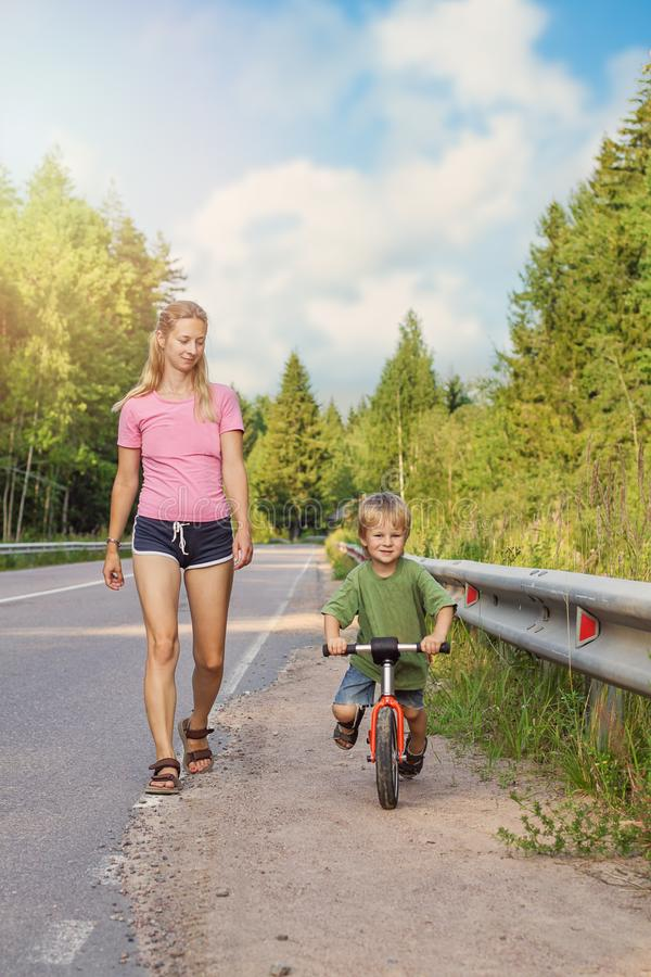 Actief blondemamma die met jong geitje met fiets lopen De sport van de familie stock afbeeldingen