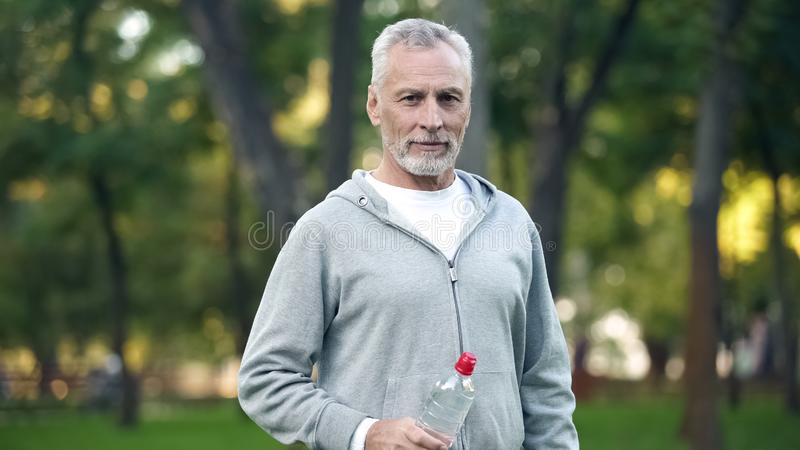 Actief grootvader drinkwater na training in park, gezondheidszorg, sport stock fotografie