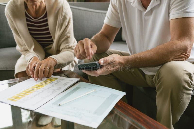 Actief hoger paar die binnenlandse rekeningen op bank in woonkamer berekenen bij comfortabel huis royalty-vrije stock foto's