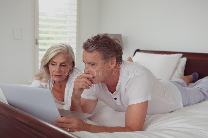 Actief hoger paar die laptop met behulp van terwijl het liggen op bed in slaapkamer bij comfortabel huis stock afbeeldingen