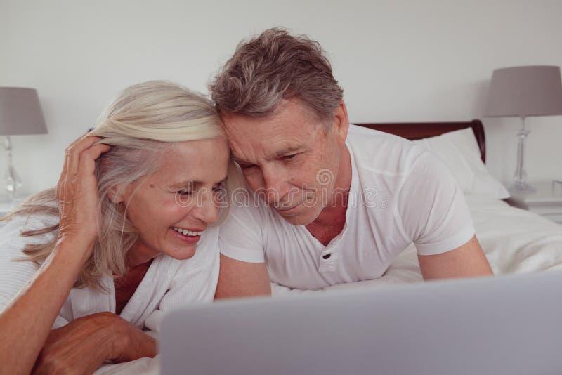 Actief hoger paar die laptop met behulp van terwijl het liggen op bed in slaapkamer bij comfortabel huis royalty-vrije stock afbeelding