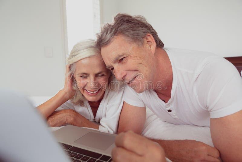 Actief hoger paar die laptop met behulp van terwijl het liggen op bed in slaapkamer bij comfortabel huis royalty-vrije stock afbeeldingen