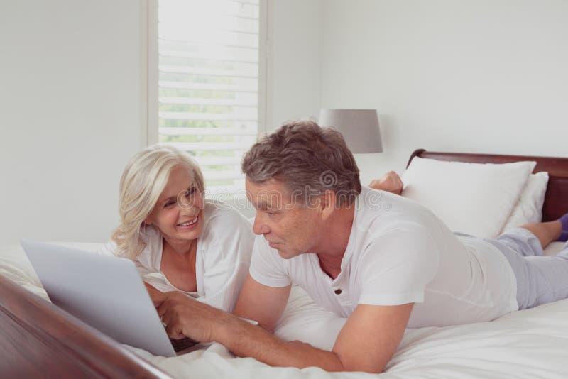 Actief hoger paar die laptop met behulp van terwijl het liggen op bed in slaapkamer bij comfortabel huis royalty-vrije stock fotografie