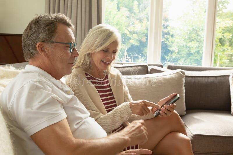 Actief hoger paar die over mobiele telefoon op bank in een comfortabel huis bespreken stock foto's