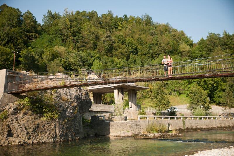 Actief jong paar op een brug over alpiene rivier op de hete zomer royalty-vrije stock foto's