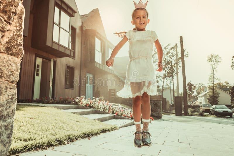 Actief mager meisje die in vrij witte kleding op de straat springen stock foto