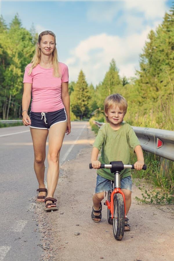 Actief mamma die met jong geitje met fiets lopen stock afbeeldingen