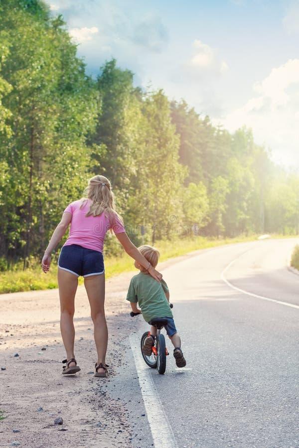 Actief mamma die met jong geitje met fiets lopen De sport van de familie royalty-vrije stock afbeeldingen
