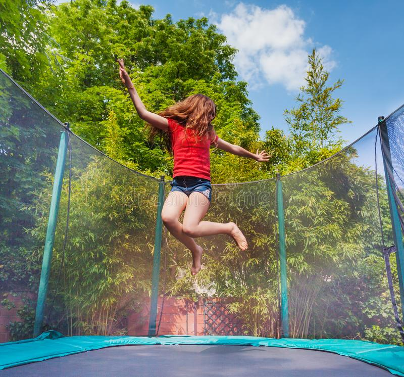 Actief meisje die op trampoline in openlucht springen royalty-vrije stock afbeelding