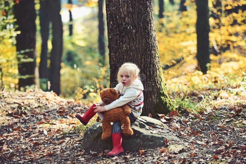Actief meisje met teddybeer in de herfst bos Actieve rust en activiteit op verse lucht in hout stock foto's