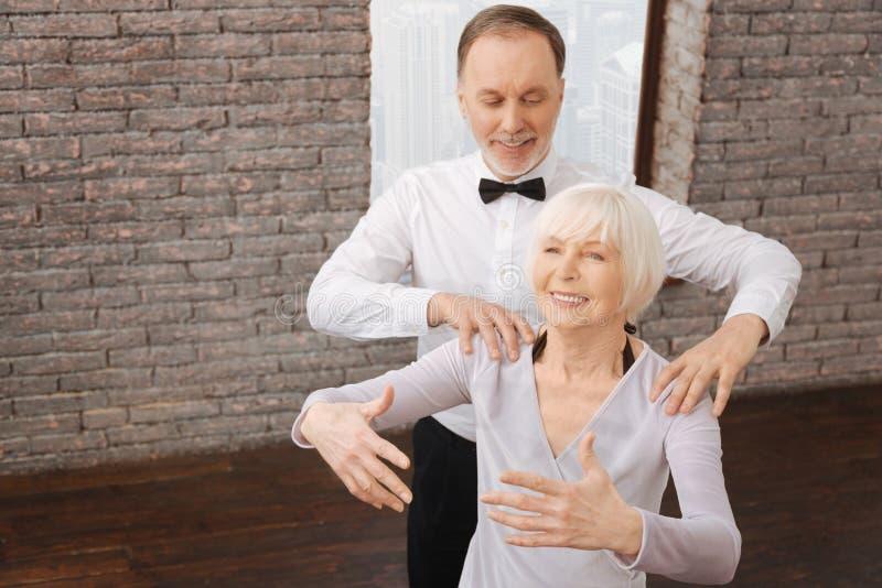 Actief oud paar die in interactie in de dansstudio presteren stock afbeeldingen