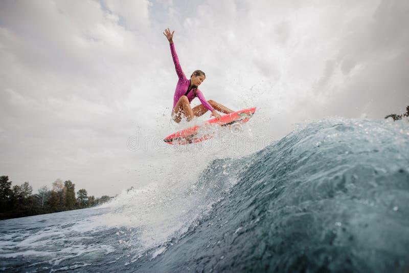 Actief tienermeisje in het roze zwempak die op de sinaasappel springen stock fotografie