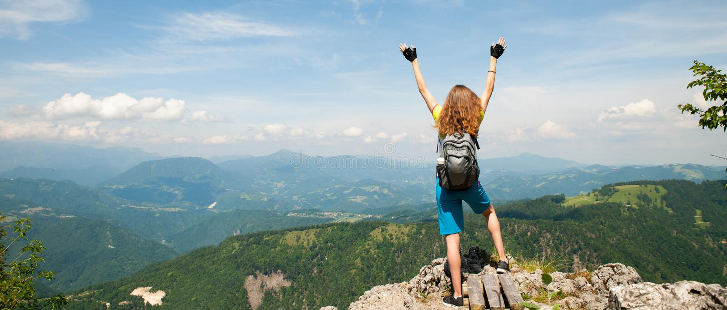 Actief vrouwen gesturing succes na het beklimmen van een berg stock afbeelding