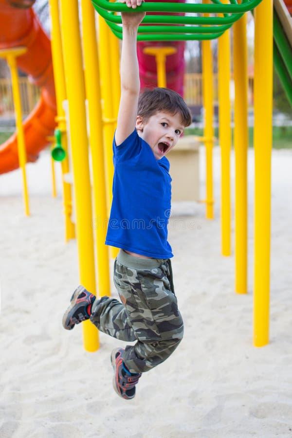 Actief weinig jongen die op wildernisgymnastiek hangen stock fotografie