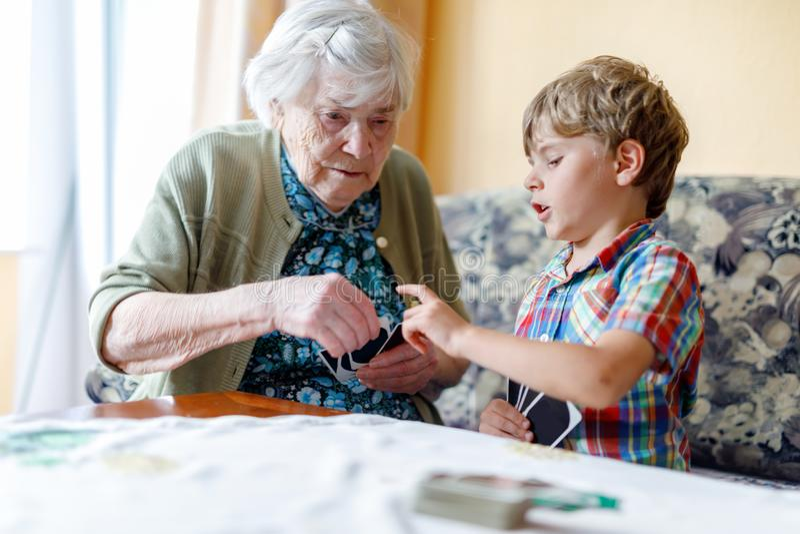 Actief weinig peuterjong geitjejongen en groot spel van de grootmoederspeelkaart samen thuis stock foto