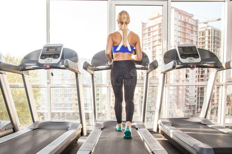 Actieve atletische vrouw met perfect lichaam, die op renbaan binnen aanstoten royalty-vrije stock fotografie