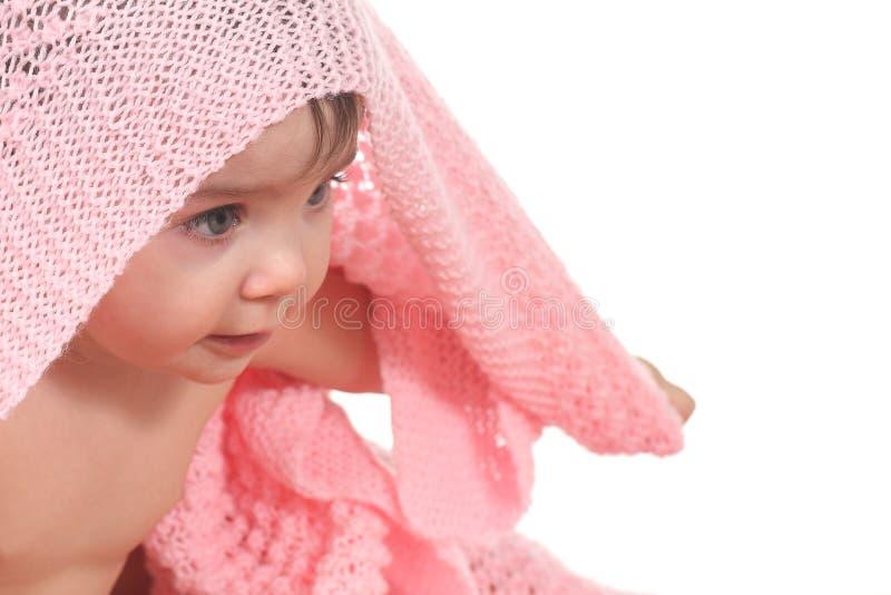 Actieve baby onder een roze deken stock foto's