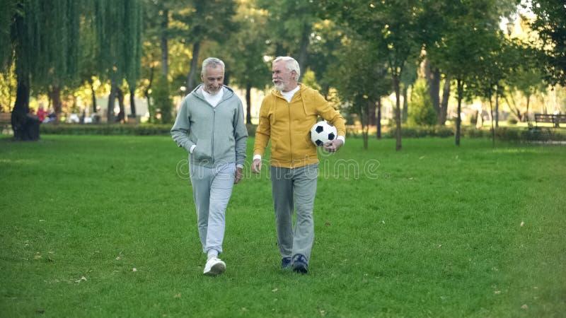Actieve bejaarden die in park met voetbal, sporthobby, gezondheidszorg lopen royalty-vrije stock foto's