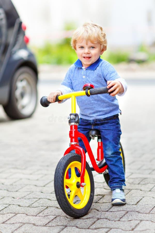 Actieve blonde jong geitjejongen in kleurrijke kleren die saldo en de fiets van de leerling drijven of fiets in binnenlandse tuin stock afbeeldingen