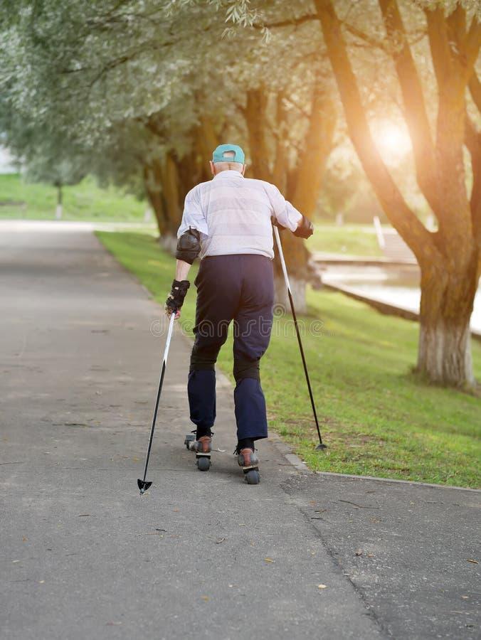 Actieve gepensioneerde die en extreme draaien rollerblading maken De herfstgangen in de verse lucht Actieve oude mensen stock afbeelding