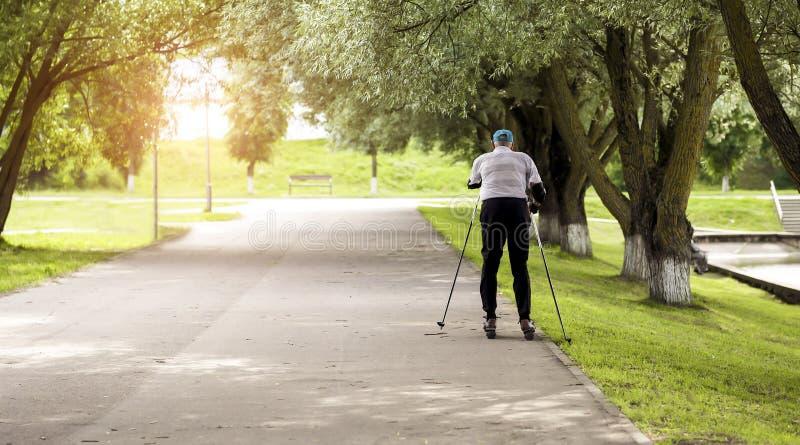 Actieve gepensioneerde die en extreme draaien rollerblading maken De herfstgangen in de verse lucht Actieve oude mensen stock afbeeldingen