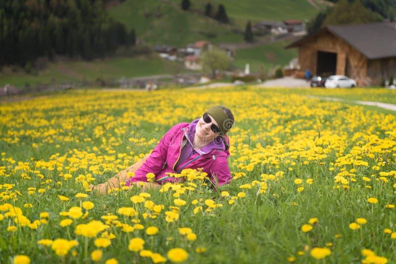 Actieve gezonde vrouw die rust op mooie die weide hebben met bloemen wordt behandeld royalty-vrije stock fotografie