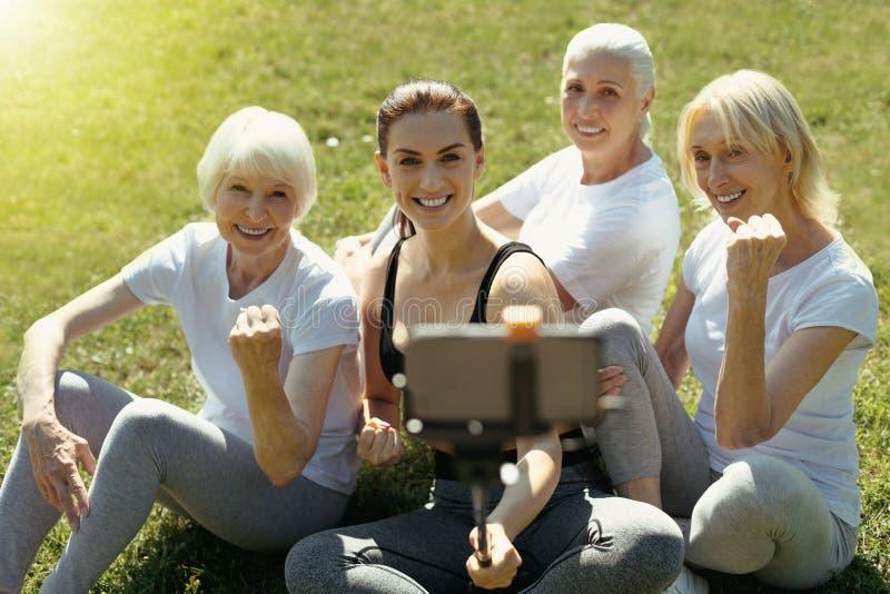 Actieve hogere dames die voor selfie met bus stellen stock foto's