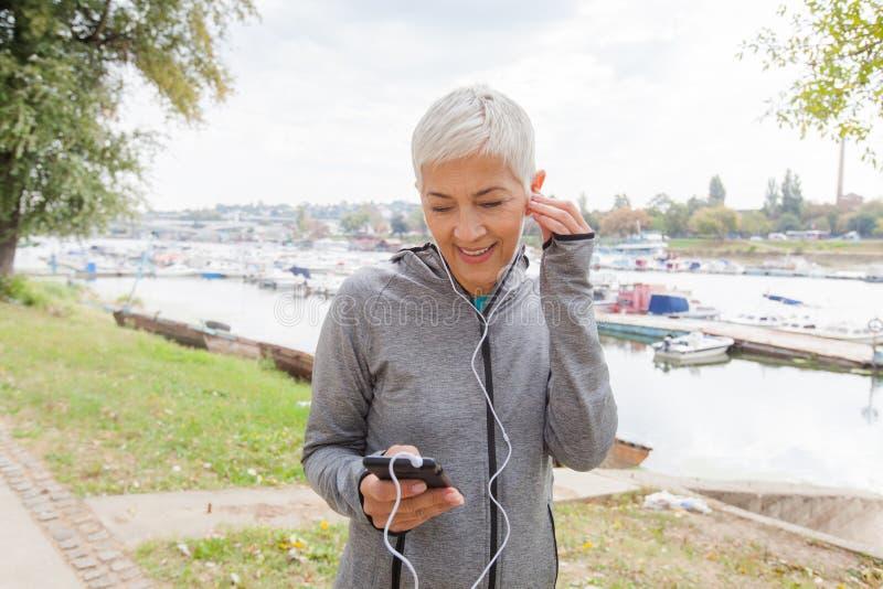 Actieve Hogere Lopende Vrouw het Luisteren Muziek royalty-vrije stock afbeelding