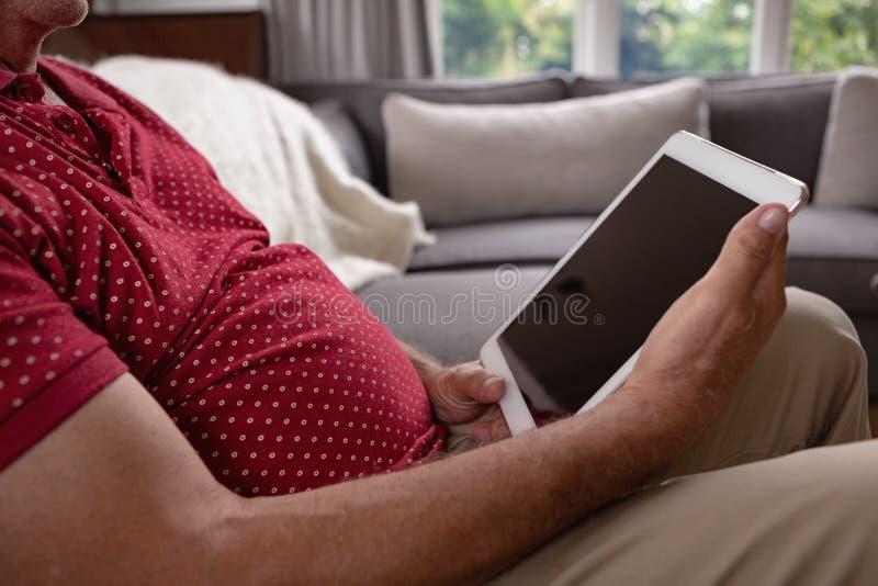 Actieve hogere mens die digitale tablet op bank in een comfortabel huis gebruiken royalty-vrije stock fotografie