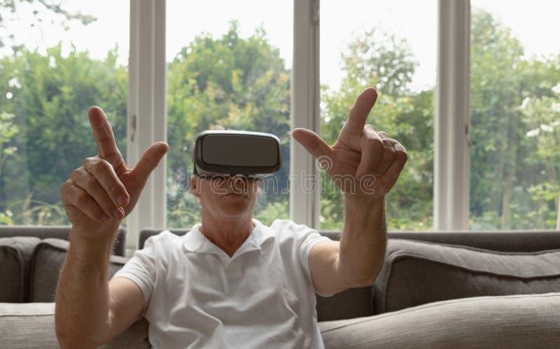 Actieve hogere mens die virtuele werkelijkheidshoofdtelefoon op bank in een comfortabel huis met behulp van stock foto's