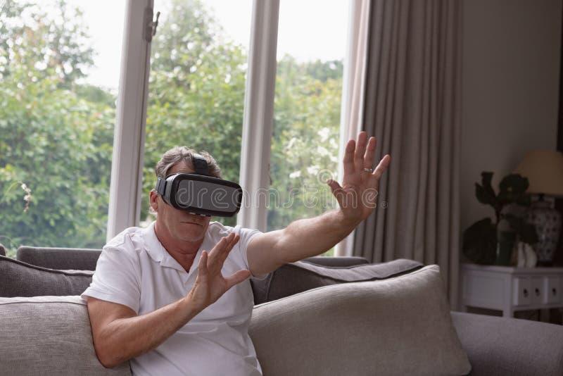 Actieve hogere mens die virtuele werkelijkheidshoofdtelefoon op bank in een comfortabel huis met behulp van royalty-vrije stock afbeelding