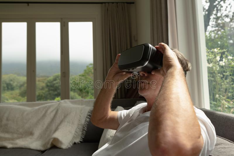 Actieve hogere mens die virtuele werkelijkheidshoofdtelefoon op bank in een comfortabel huis met behulp van royalty-vrije stock foto
