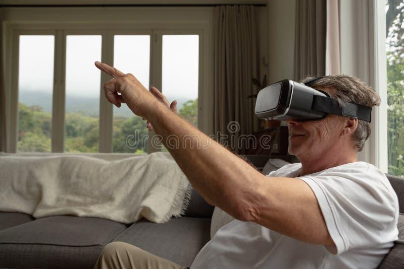 Actieve hogere mens die virtuele werkelijkheidshoofdtelefoon op bank in een comfortabel huis met behulp van royalty-vrije stock afbeeldingen