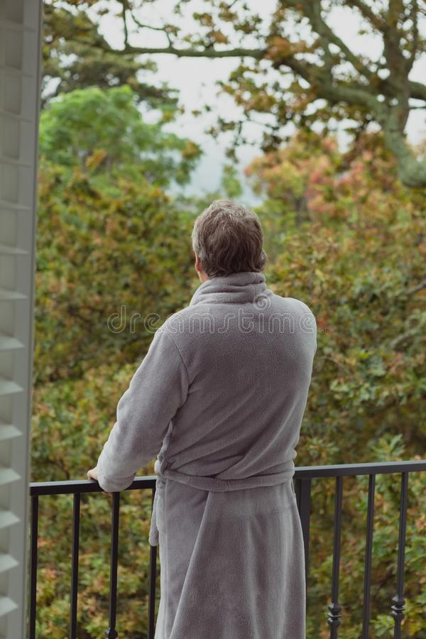 Actieve hogere mens die zich in balkon in een comfortabel huis bevinden stock foto