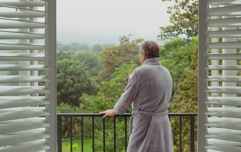 Actieve hogere mens die zich in balkon in een comfortabel huis bevinden royalty-vrije stock foto's