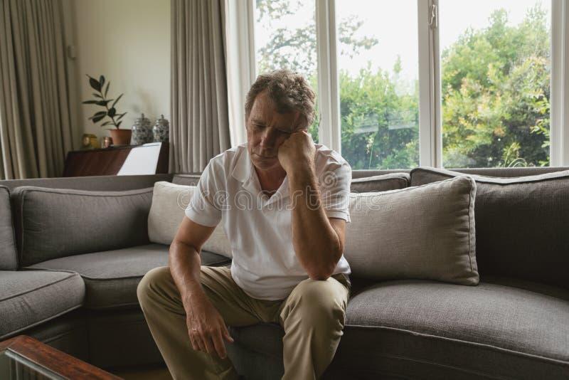 Actieve hogere mens met hand op gezichtszitting op bank in een comfortabel huis stock fotografie