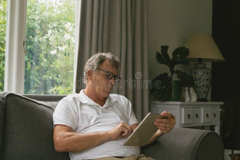 Actieve hogere mensenzitting op bank en het gebruiken van digitale tablet in woonkamer bij comfortabel huis royalty-vrije stock fotografie