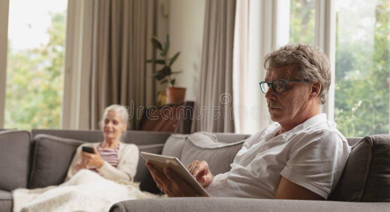 Actieve hogere mensenzitting op bank en het gebruiken van digitale tablet in woonkamer bij comfortabel huis royalty-vrije stock afbeeldingen